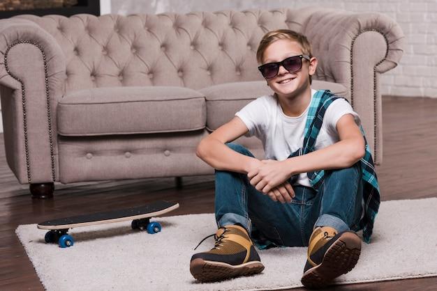 Vista frontale del ragazzo con gli occhiali da sole che si siedono sul pavimento