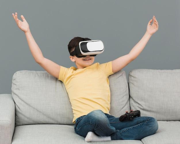 Vista frontale del ragazzo felice che usando la cuffia avricolare di realtà virtuale