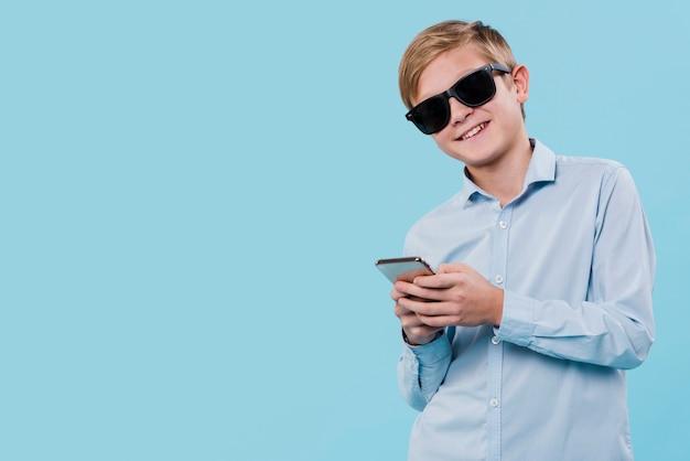 Vista frontale del ragazzo moderno con gli occhiali da sole e lo spazio della copia