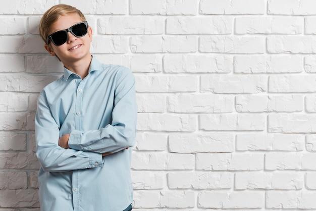 Vista frontale del ragazzo moderno con gli occhiali da sole