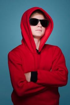 Vista frontale del ragazzo moderno con la posa degli occhiali da sole