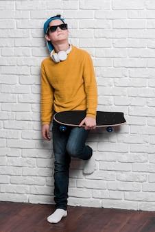 Vista frontale del ragazzo moderno con occhiali da sole con skateboard