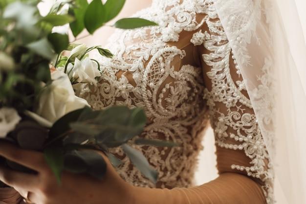 Vista frontale del ricamo sul corsetto del vestito da sposa e bouquet da sposa di eustomas bianchi