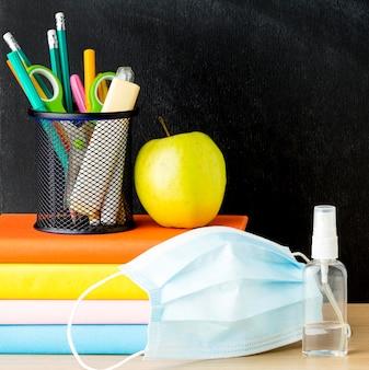 Vista frontale del ritorno a materiale scolastico con maschera medica e libri