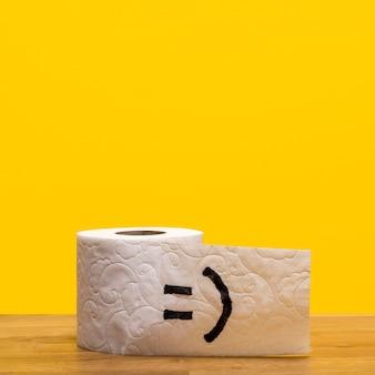 Vista frontale del rotolo di carta igienica con faccina e copia spazio