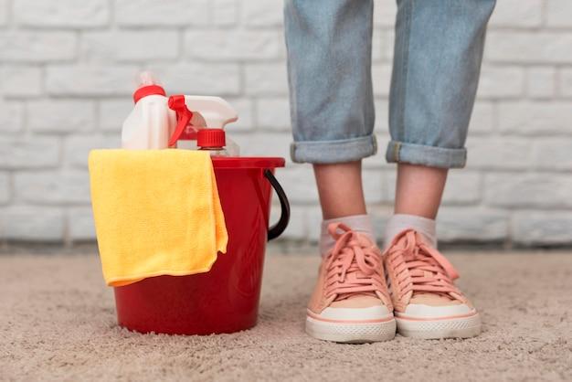 Vista frontale del secchio con prodotti per la pulizia accanto alla donna