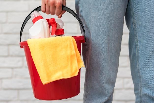 Vista frontale del secchio della tenuta della donna con le soluzioni di pulizia