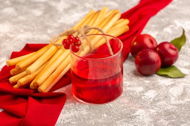 Vista frontale del succo di prugna con prugne fresche e cracker stick su frutta bianca color vitamina estate
