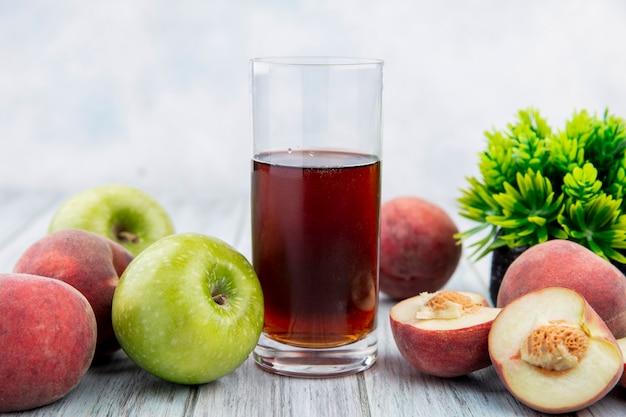 Vista frontale del succo in un bicchiere con frutta fresca come la pesca di mele sulla superficie bianca