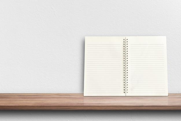 Vista frontale del taccuino bianco sullo scaffale per esposizione del prodotto o modello di progettazione.