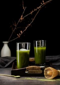 Vista frontale del tè matcha in bicchieri sul vassoio