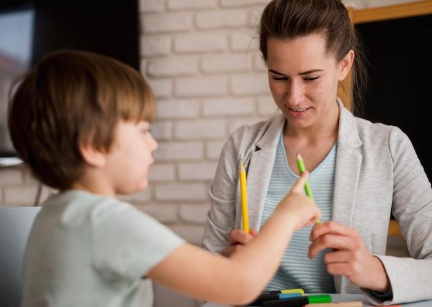 Vista frontale del tutor che insegna al bambino a contare