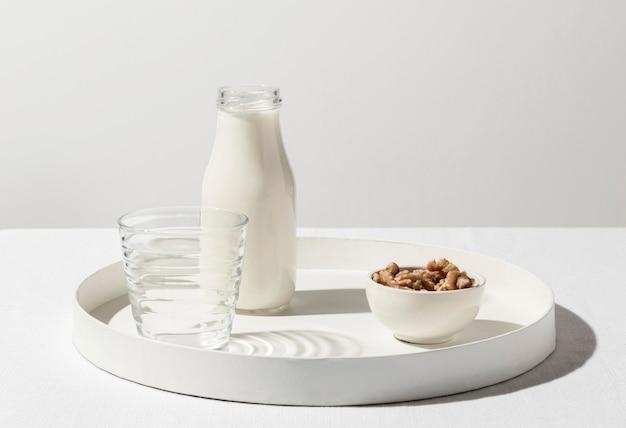 Vista frontale del vassoio con bottiglia di latte e noci