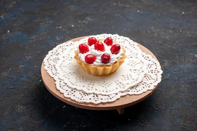 Vista frontale deliziosa piccola torta con crema e frutti rossi sulla frutta dolce superficie scura