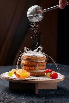 Vista frontale deliziosi biscotti sandwich legati gustosi con frutta a fette e zucchero in polvere sulla torta da scrivania blu scuro