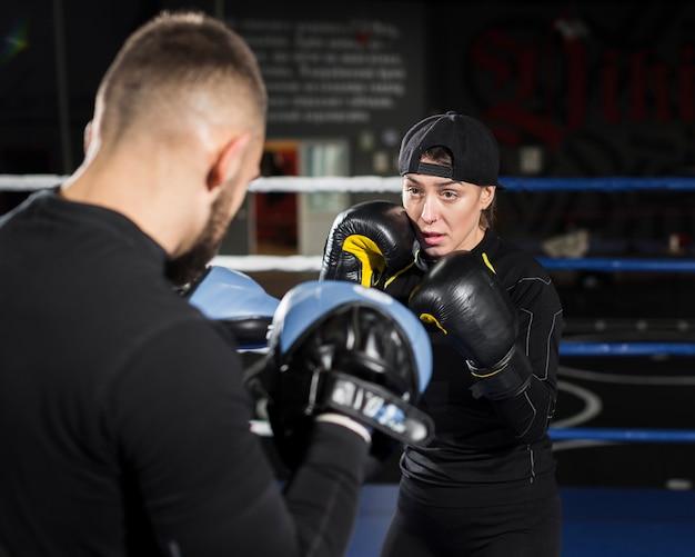 Vista frontale dell'addestramento femminile del pugile mentre indossando i guanti protettivi