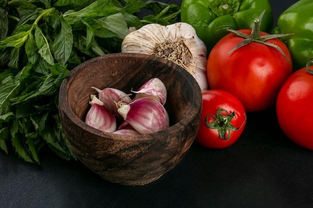 Vista frontale dell'aglio in una ciotola con pomodori e menta su una superficie nera