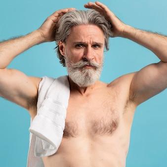 Vista frontale dell'anziano con l'asciugamano dopo la doccia