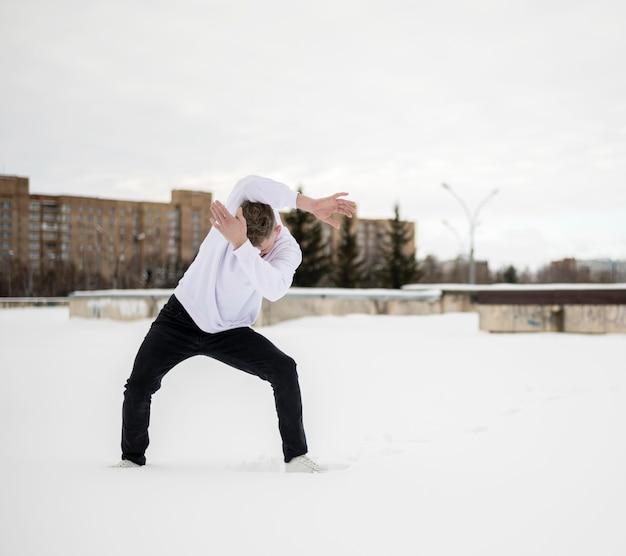 Vista frontale dell'artista hip-hop maschio che posa nella neve