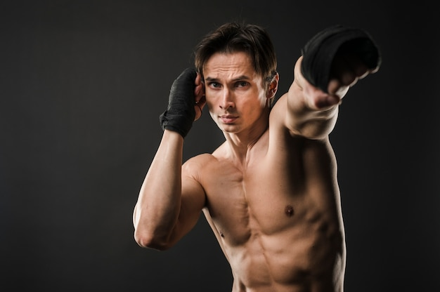 Vista frontale dell'atleta senza camicia con guantoni da boxe