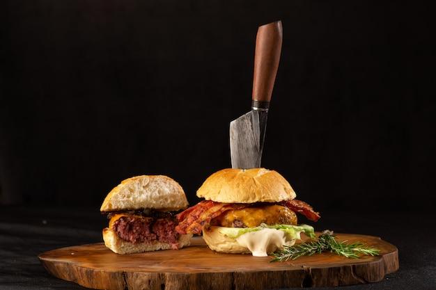 Vista frontale dell'hamburger casalingo rustico con la cipolla su una tavola di legno