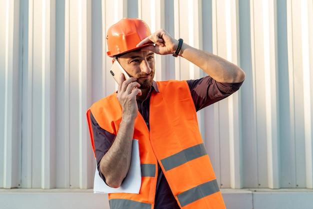 Vista frontale dell'operaio che parla sul telefono