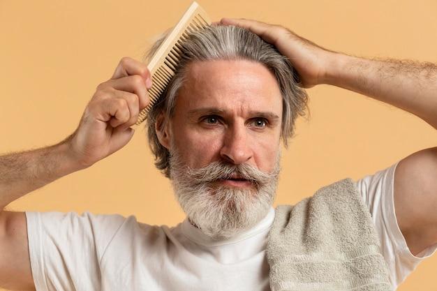 Vista frontale dell'uomo anziano con la barba che si pettina i capelli