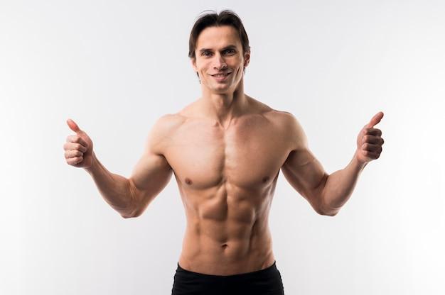Vista frontale dell'uomo atletico che posa senza camicia e che dà i pollici su