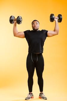 Vista frontale dell'uomo atletico che tiene i pesi