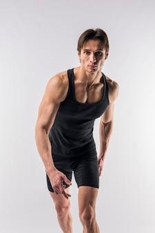 Vista frontale dell'uomo atletico nella posa della tuta