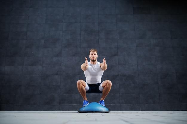 Vista frontale dell'uomo barbuto muscolare caucasico bello che fa esercizio tozzo sulla palla di bosu. sullo sfondo è il muro grigio.