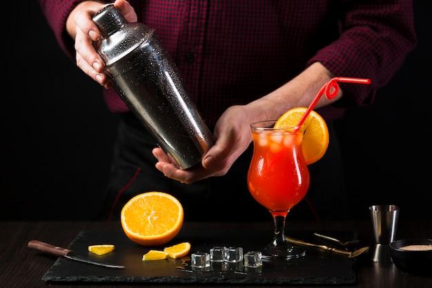 Vista frontale dell'uomo che agita cocktail