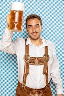 Vista frontale dell'uomo che alza la pinta di birra