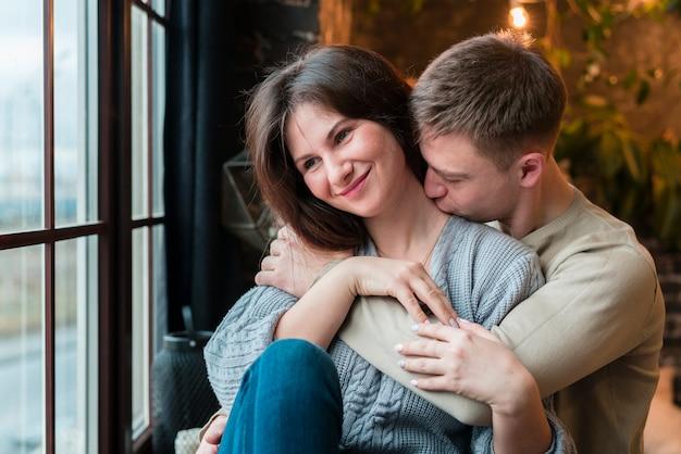Vista frontale dell'uomo che bacia la ragazza di smiley sul collo