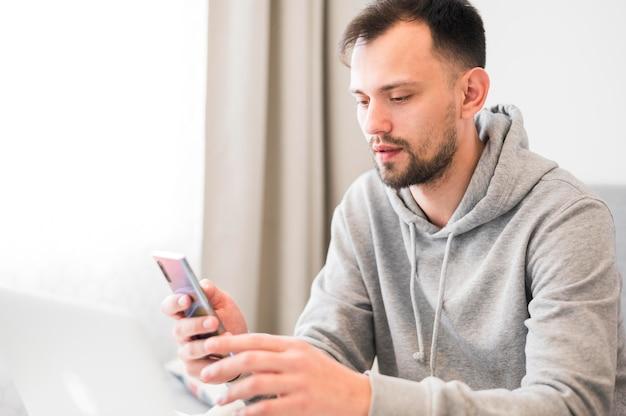 Vista frontale dell'uomo che esamina il suo telefono