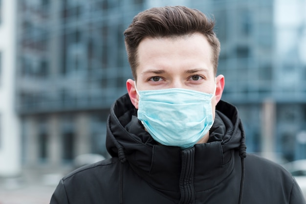 Vista frontale dell'uomo che indossa maschera medica nella città