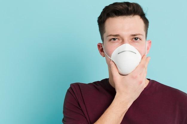 Vista frontale dell'uomo che indossa una maschera medica per prevenire il coronavirus