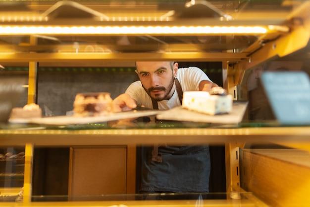 Vista frontale dell'uomo che organizza i biscotti nell'esposizione