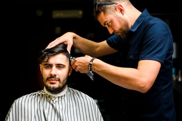 Vista frontale dell'uomo che ottiene un taglio di capelli