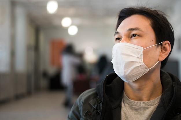 Vista frontale dell'uomo che propone con la mascherina medica