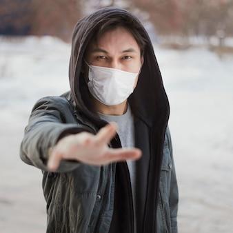 Vista frontale dell'uomo che raggiunge per qualcuno mentre indossa una maschera medica