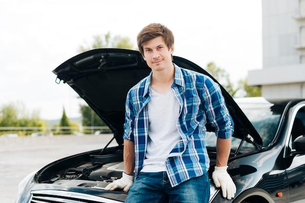 Vista frontale dell'uomo che si siede sull'automobile