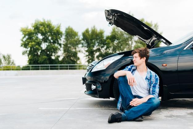 Vista frontale dell'uomo che si siede vicino all'automobile