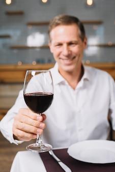 Vista frontale dell'uomo che tiene bicchiere di vino