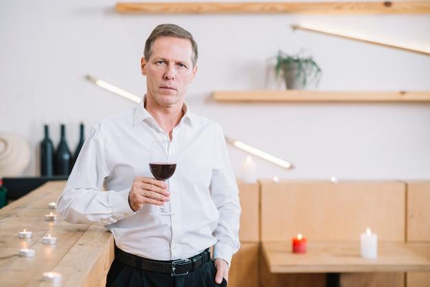 Vista frontale dell'uomo che tiene il bicchiere di vino