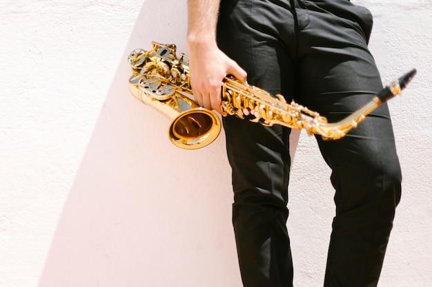 Vista frontale dell'uomo che tiene il sassofono
