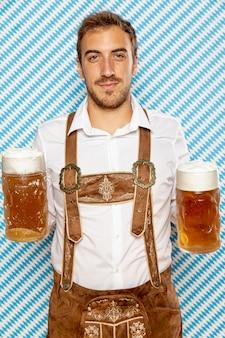 Vista frontale dell'uomo che tiene le pinte di birra