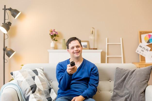 Vista frontale dell'uomo che tiene telecomando e che guarda tv