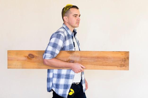 Vista frontale dell'uomo che trasporta legno