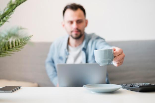 Vista frontale dell'uomo che wotking al suo computer portatile